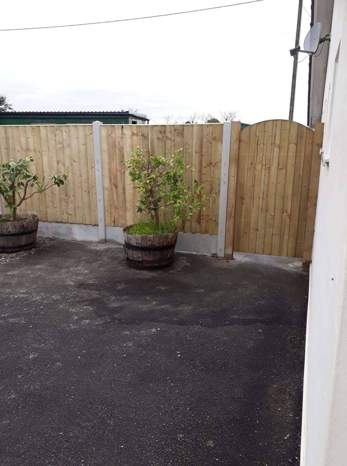 Natural panel fencing in concrete base with garden gate which has a curved top