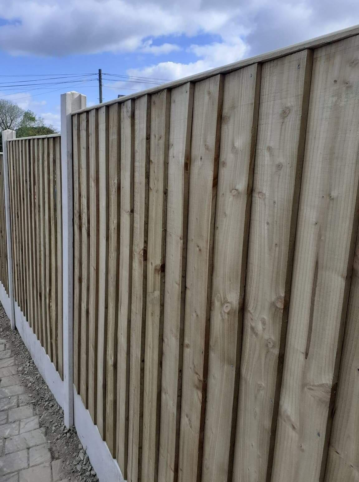 Close up of Straight edged top of panel fencing in concrete base.