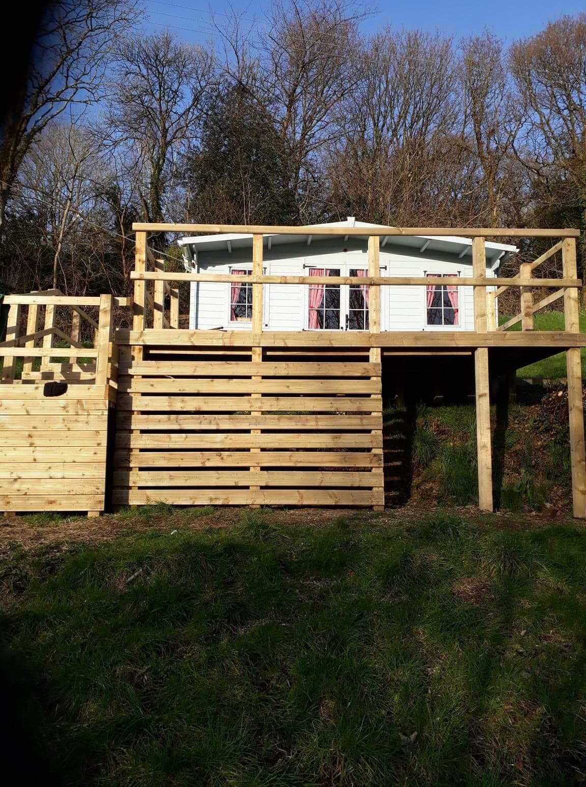 Deck built up on stilts beside cabin. Storage underneath deck.