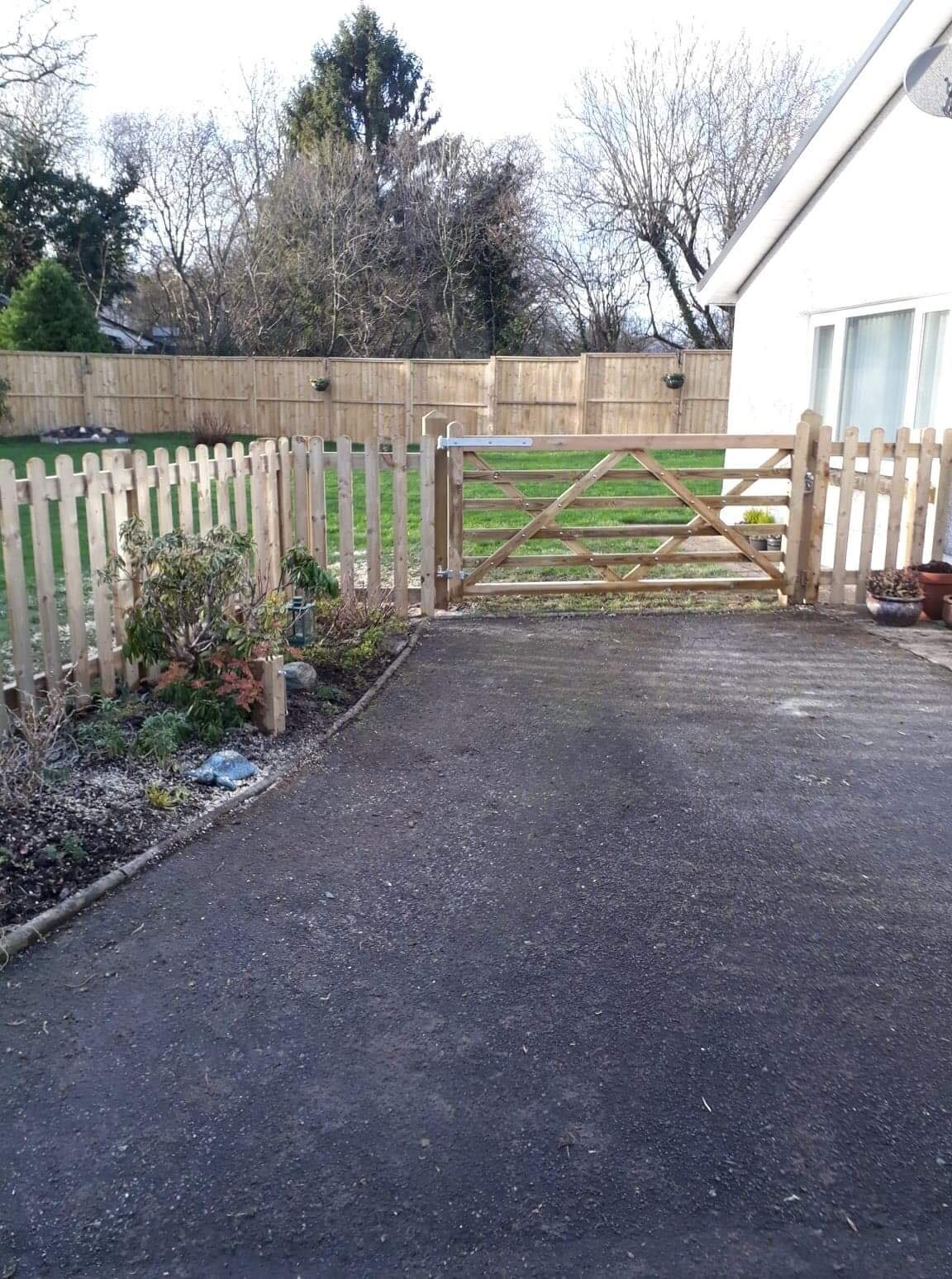 Wooden 6 bar gate and picket fence - between driveway and garden