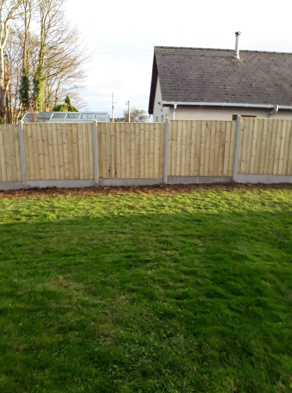 Straight edged top of panel fencing in concrete base.