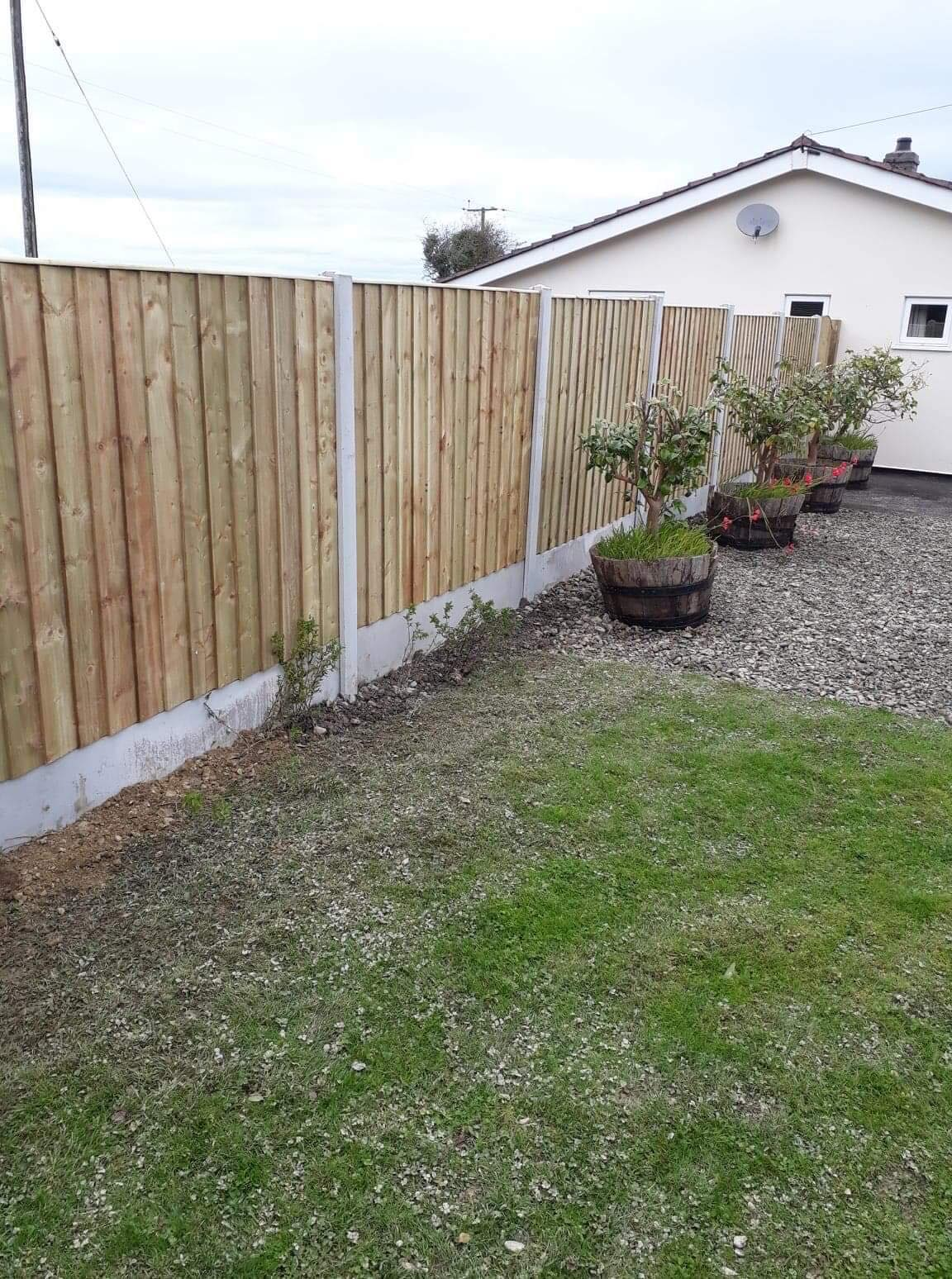Straight edged top of panel fencing in concrete base. Potted trees in front.