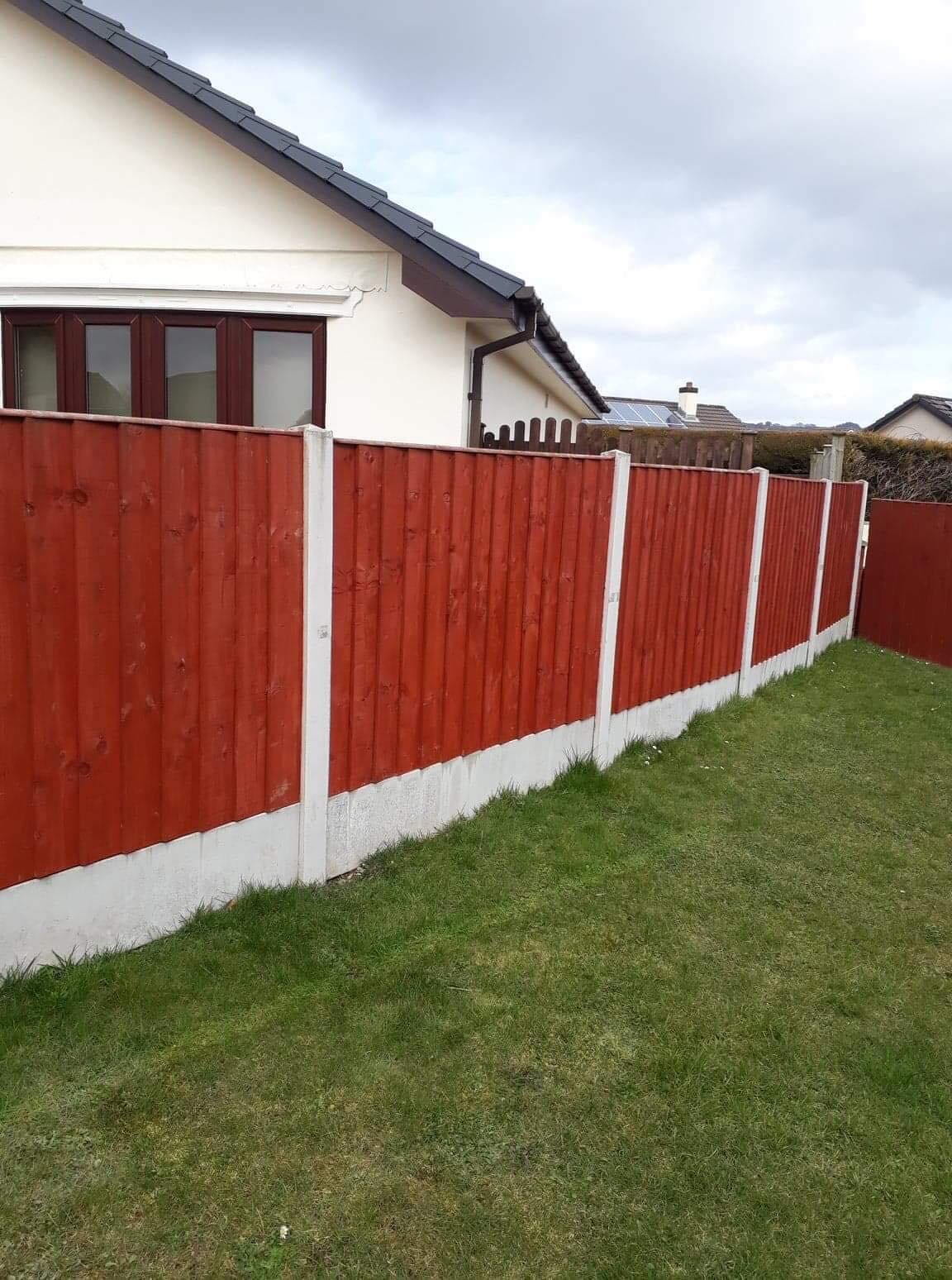 Stained panel fencing in concrete base