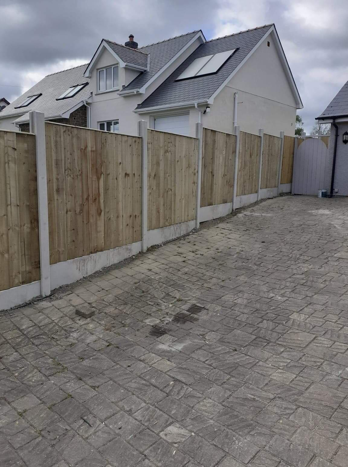 Natural panel fencing in concrete base beside driveway.