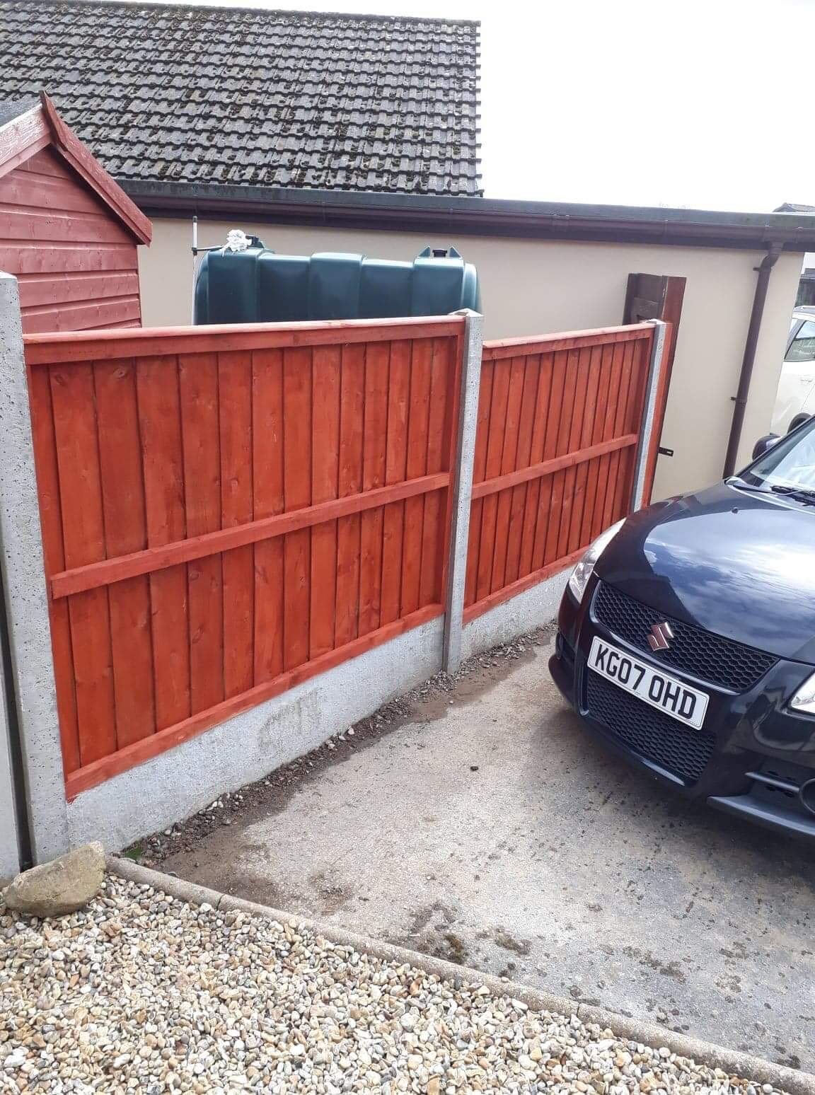 Stained panel fencing in concrete base. follow from back to the front of the house.
