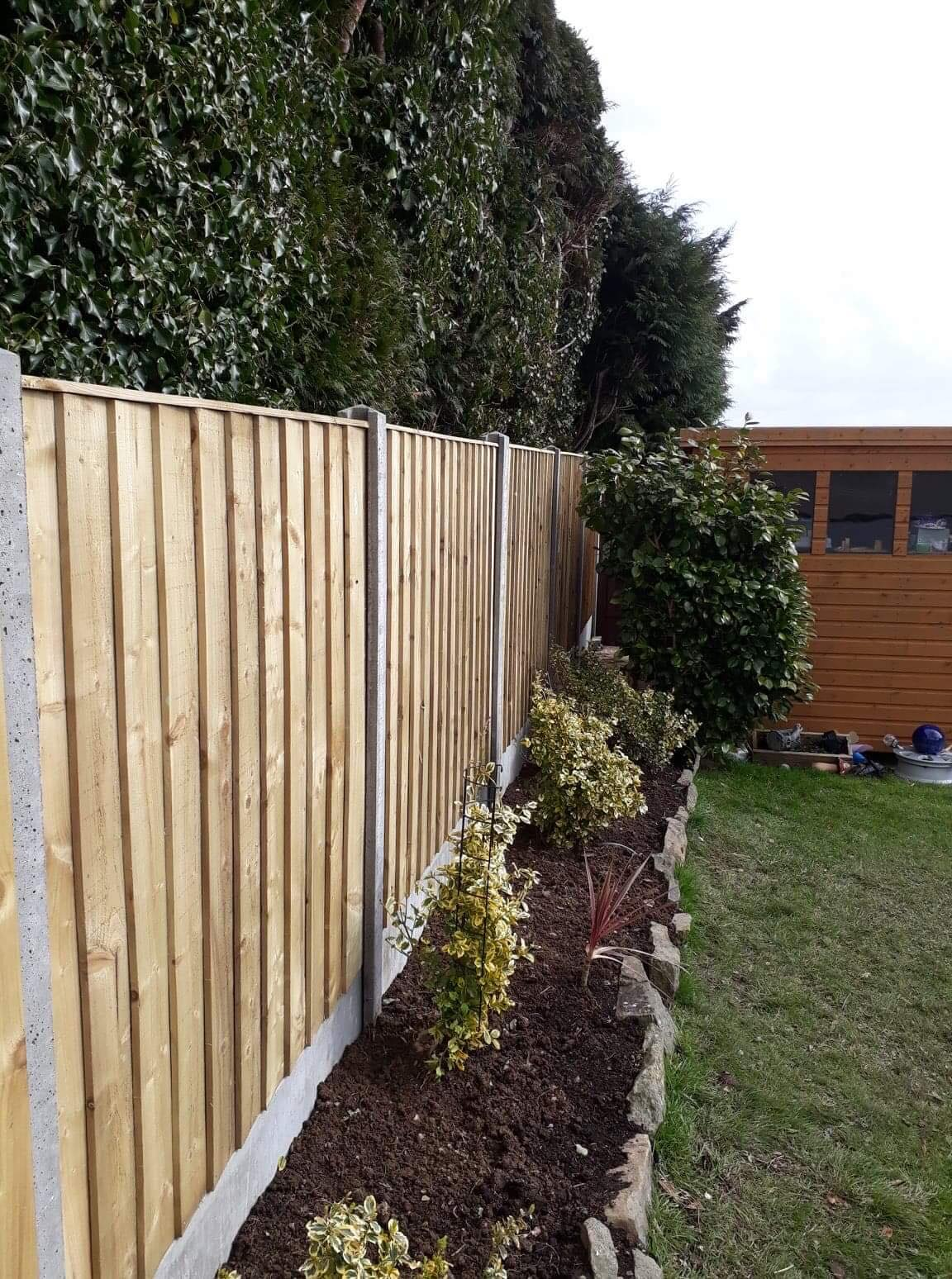 Straight edged top of panel fencing in concrete base, with planted border in front.