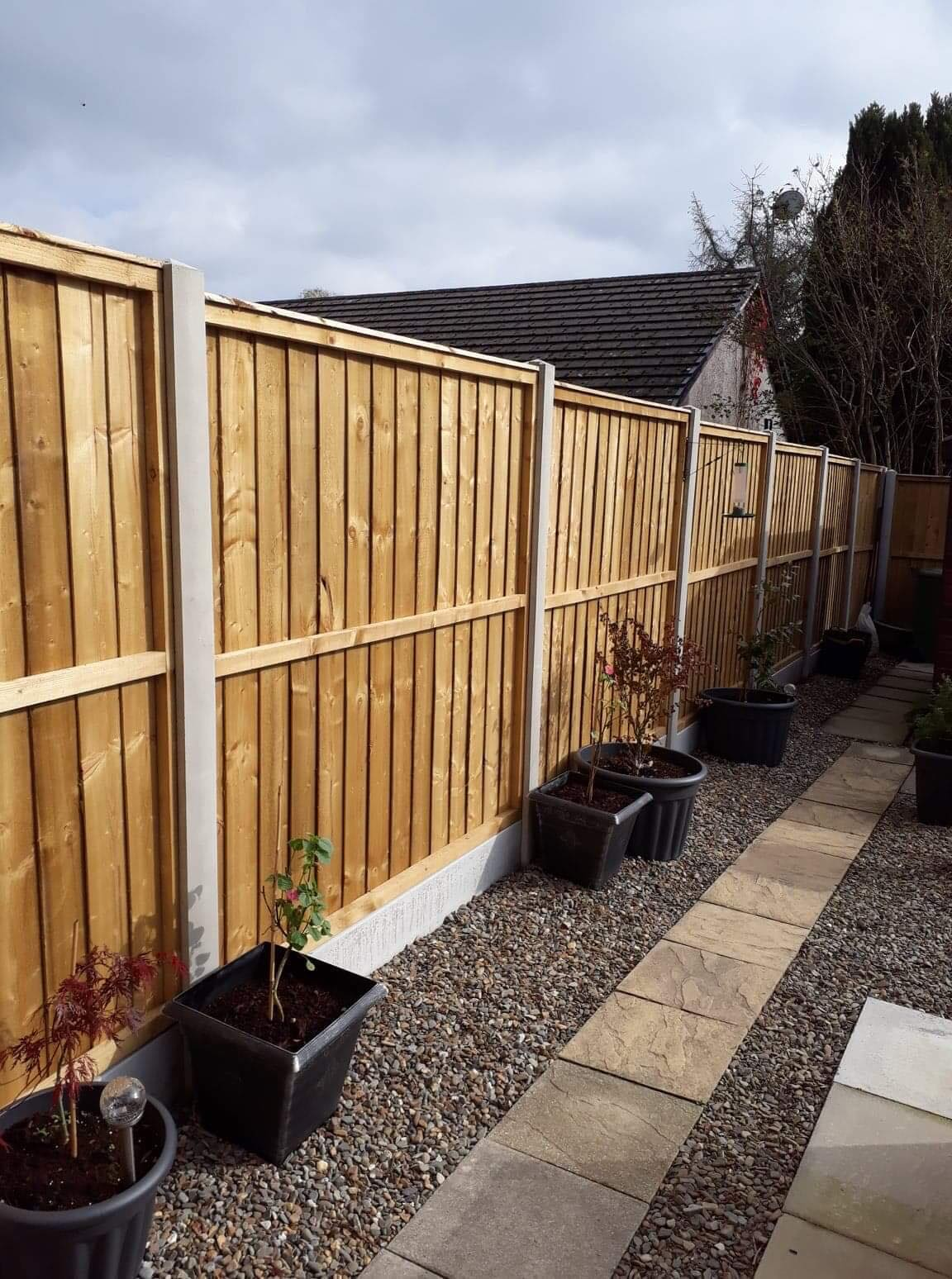 Straight edged top of panel fencing in concrete base. Potted plants in front.